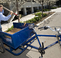 Michael Griffith of the grounds crew is pictured with a new bicycle cart that he is using instead of a motor-powered cart.